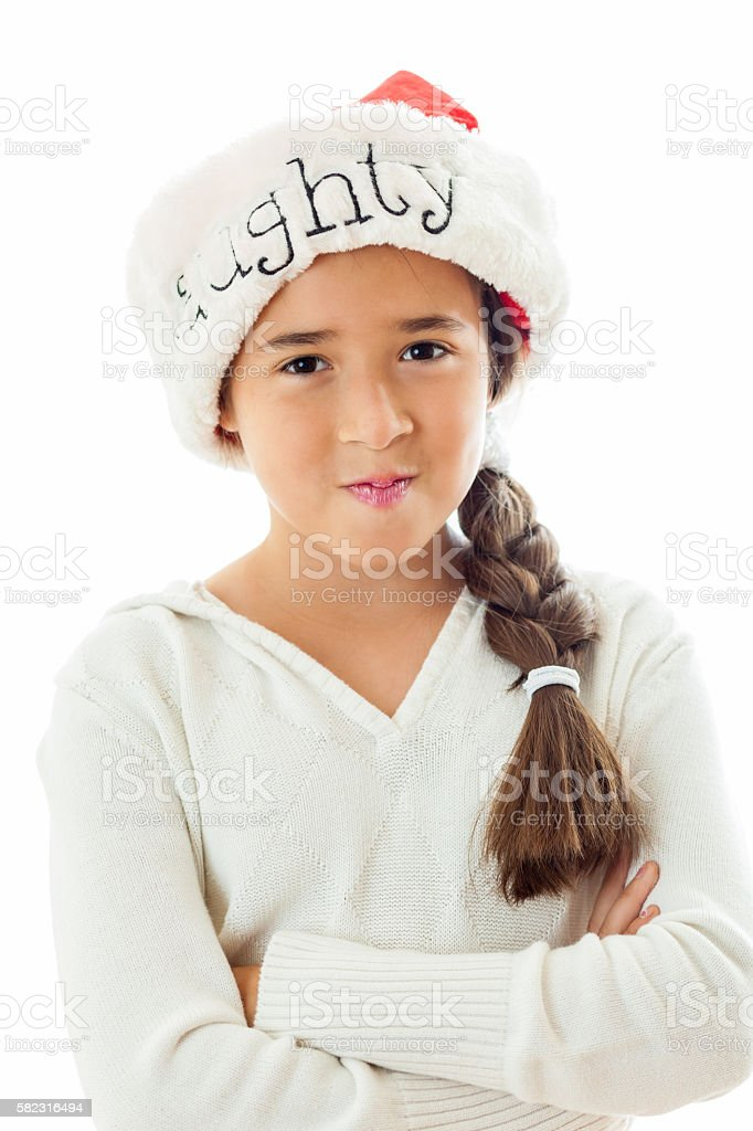Mischievous little girl wearing 'Naughty' Santa hat stock photo