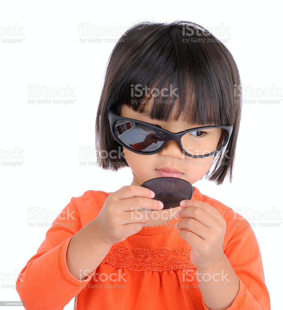 Mischievous Little Girl with Broken Sunglasses stock photo