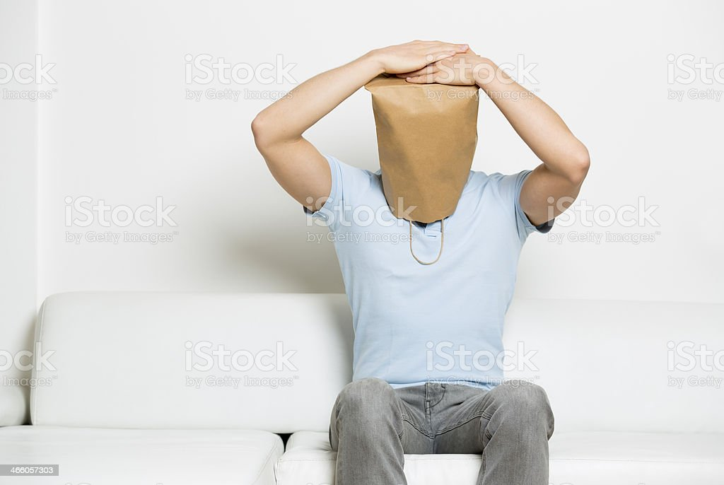 Miserable anonymous man with head covered sitting on sofa. stock photo