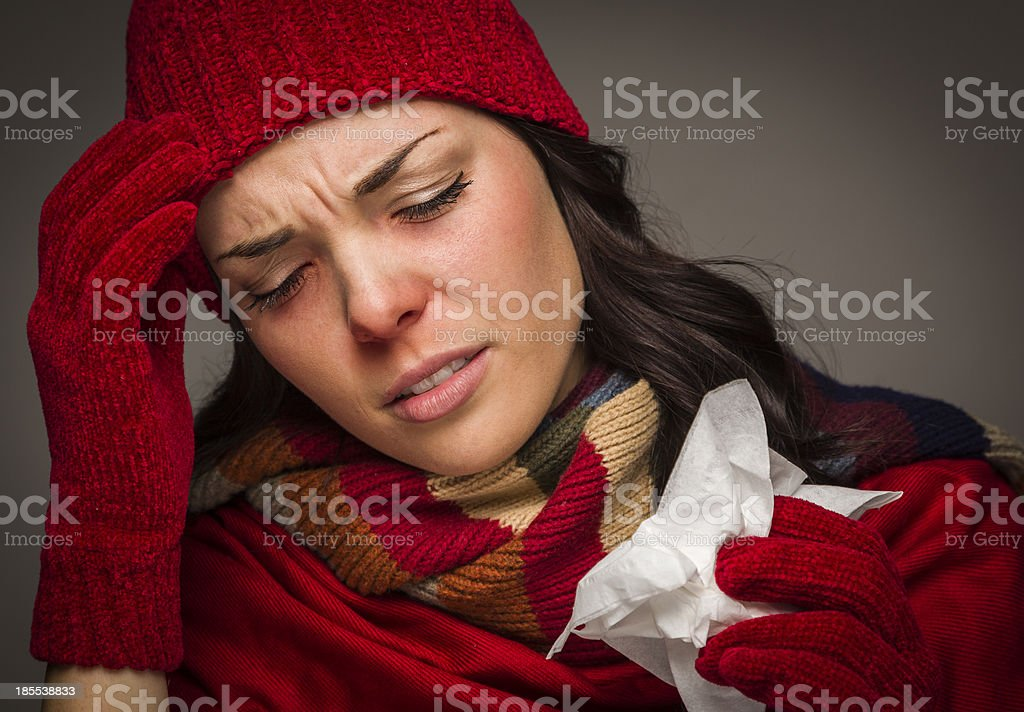 Miserable Mixed Race Woman Blowing Her Sore Nose with Tissue stock photo