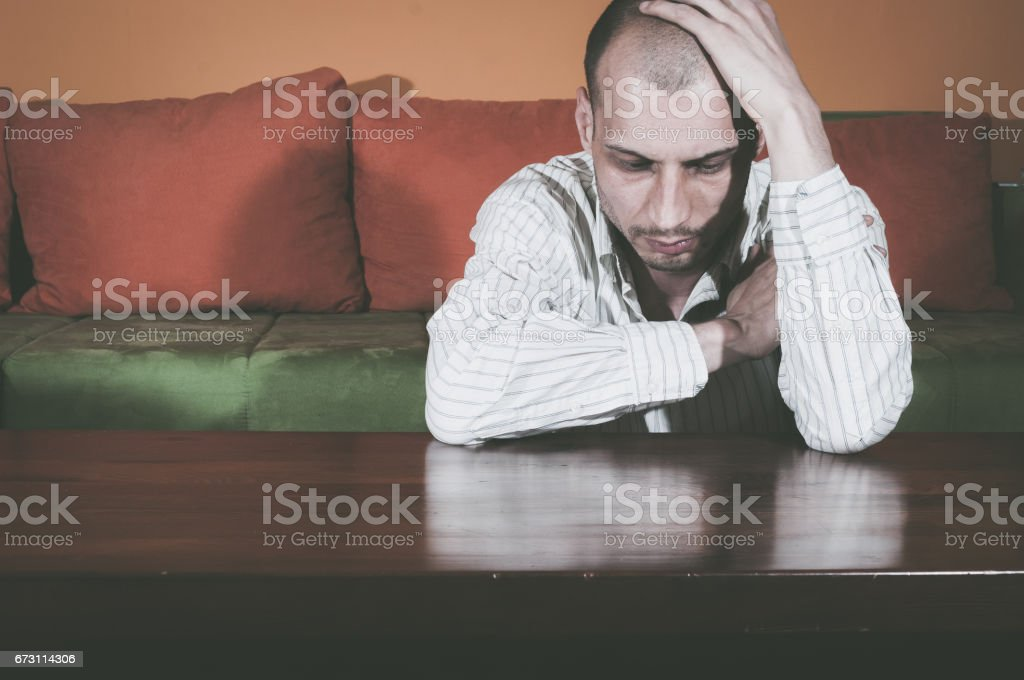 Miserable young man sitting alone in his room. Depression. stock photo