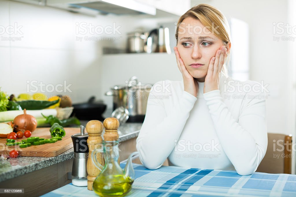 Miserable young woman in domestic kitchen stock photo