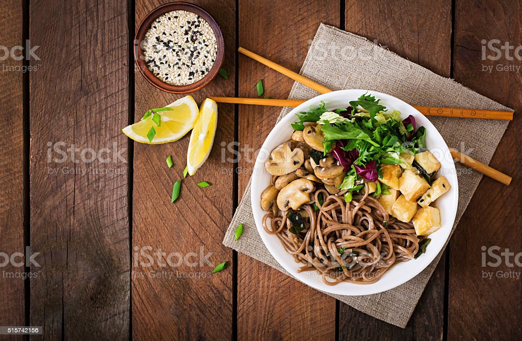 Miso and soba noodle soup with roasted tofu and mushrooms. stock photo