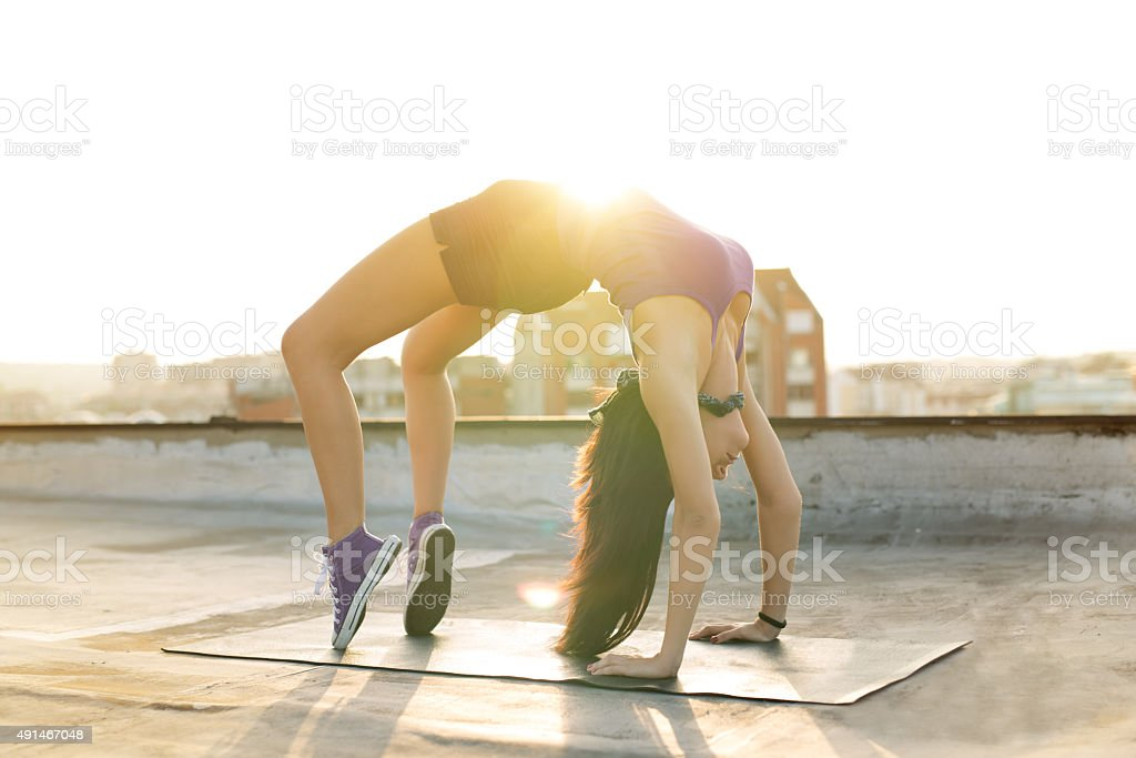 Young athletic woman doing gymnastics bridge exercise on a rooftop.