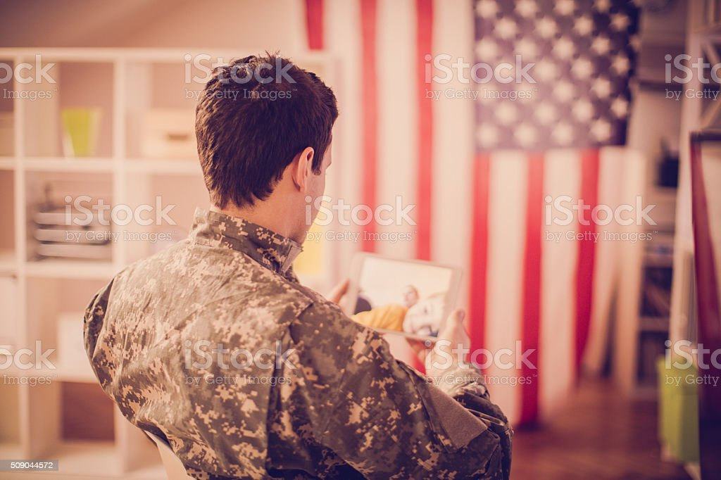 Young soldier man using a digital tablet into his office as a form of...
