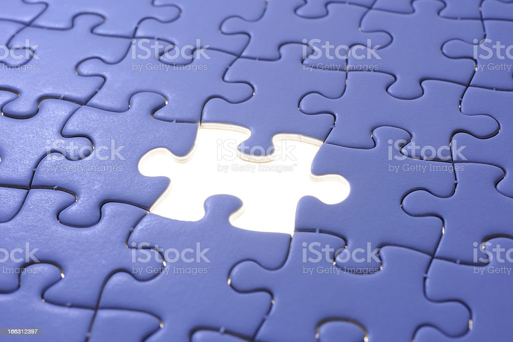 Missing piece of a blue jigsaw with light from behind royalty-free stock photo