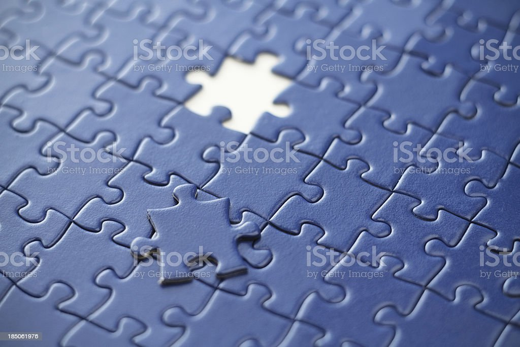 A blue puzzle with a missing piece.