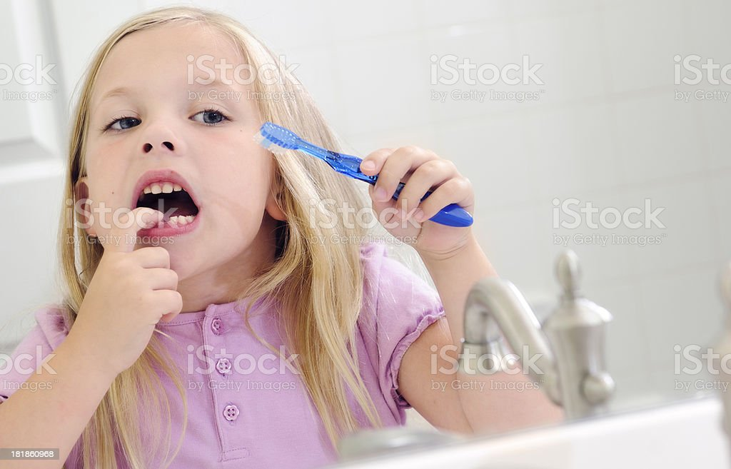 Small female child with toothbrush and missing tooth. Please see my...
