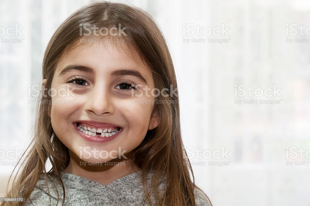 Little girl showing her first tooth that felt