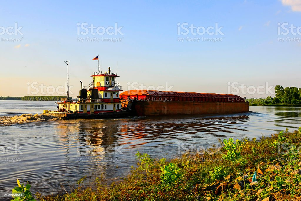 Mississippi river ditch boat pushing a loaded barge down stream stock photo