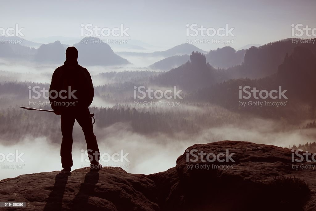 Mist in rocky mountains. Hiker stand on rocky view point stock photo