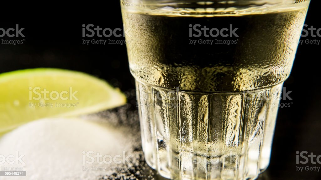 A misted glass of tequila in focus stock photo