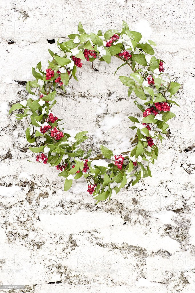 Mistletoe and Berry wreath against white wall with differential focus stock photo