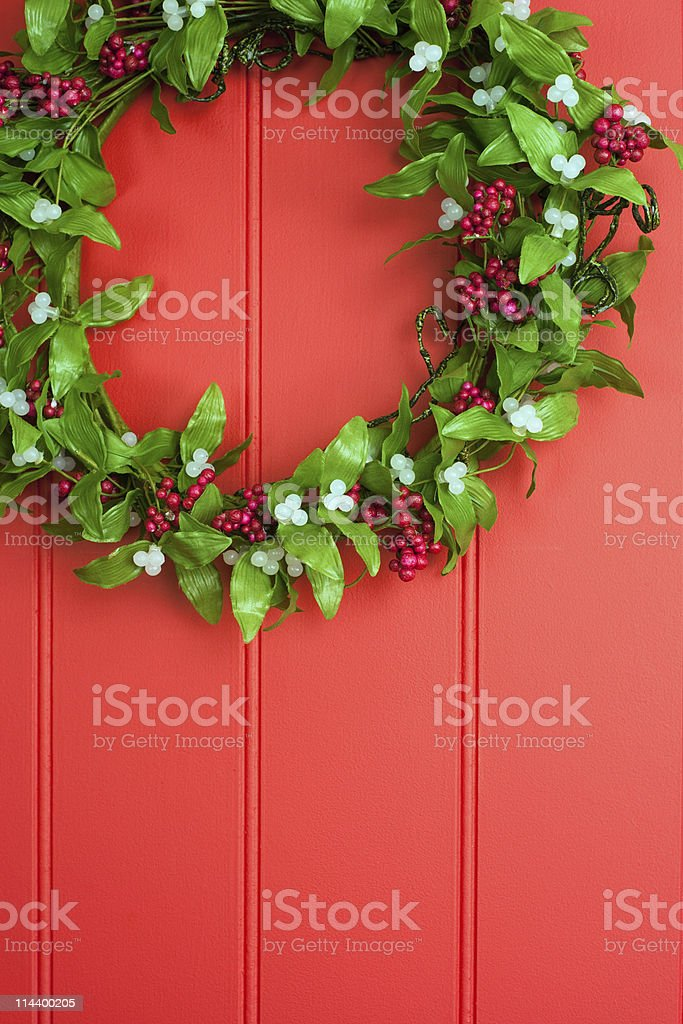 Mistletoe and berry wreath on red panelled background royalty-free stock photo
