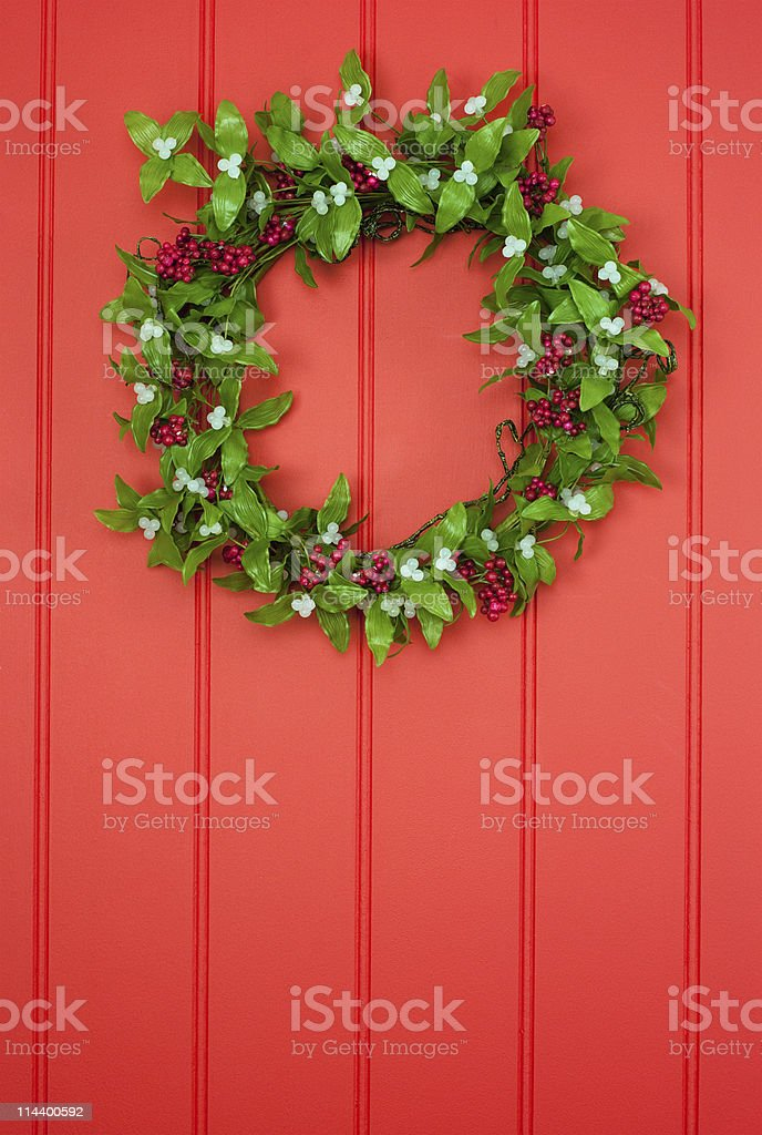 Mistletoe and berry wreath on red panelled background stock photo