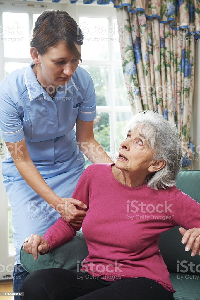 Mistreating care worker drags elderly woman up stock photo