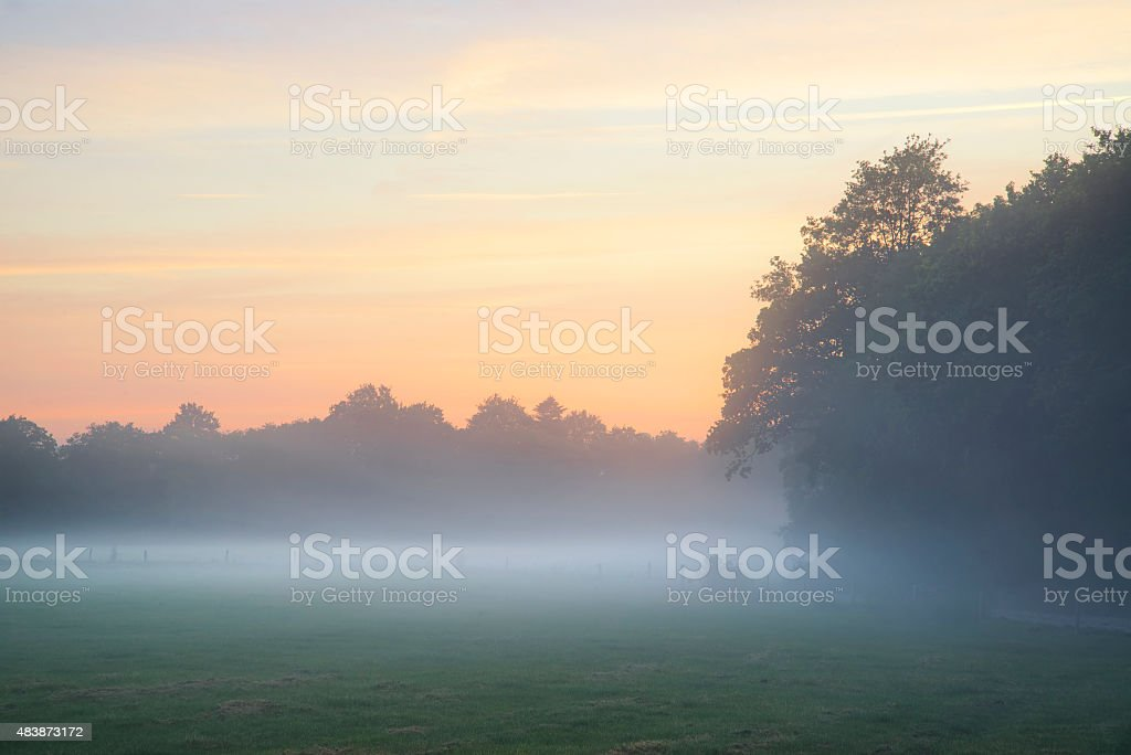 Misty landscape during sunrise in English countryside landscape stock photo