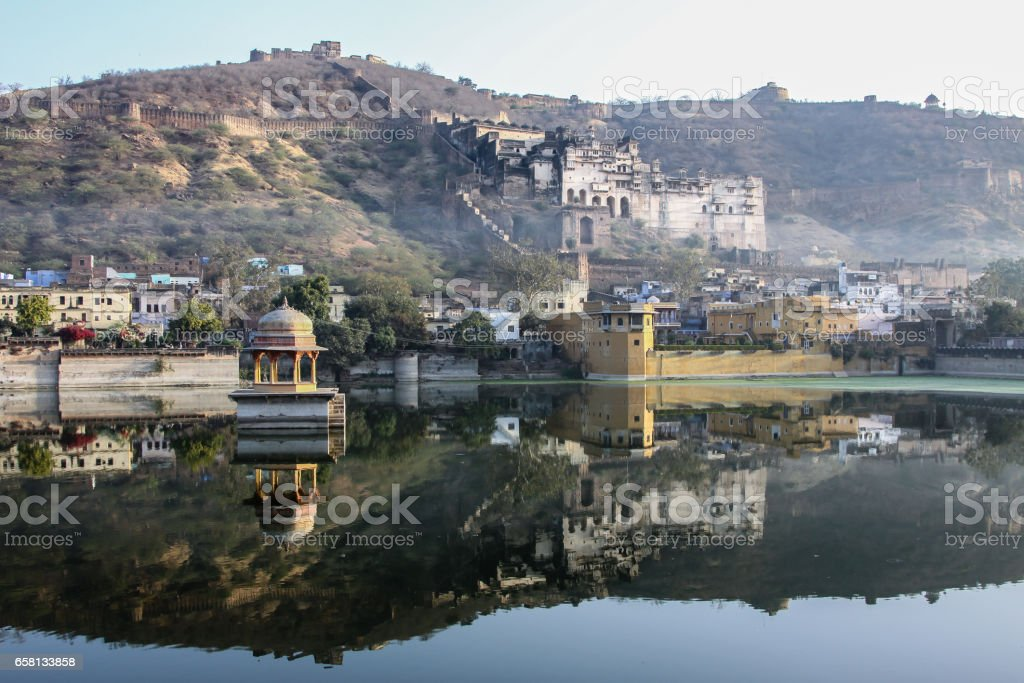 Misty morning at Nawal Sagar Lake with reflections of Bundi Palace and mountains stock photo