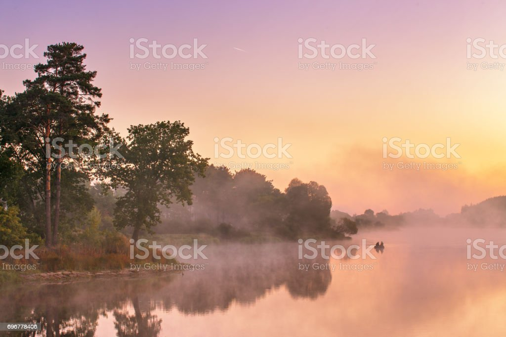 Misty morning on the lake. Fishing boat at a foggy river stock photo