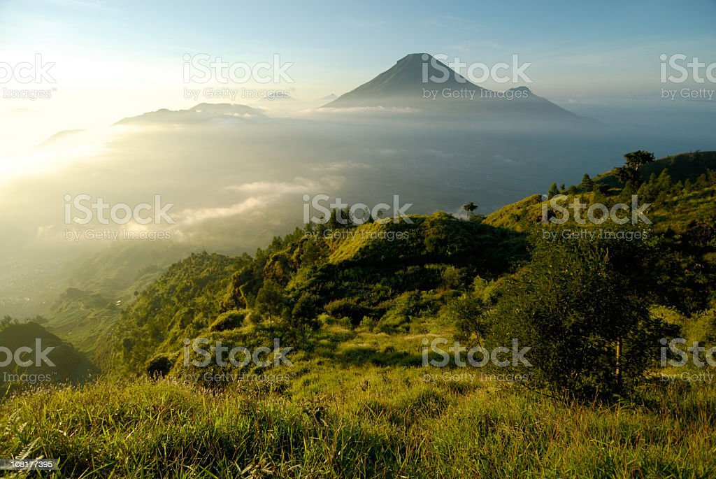 Misty mountain and volcano landscape in Indonesia at sunrise stock photo