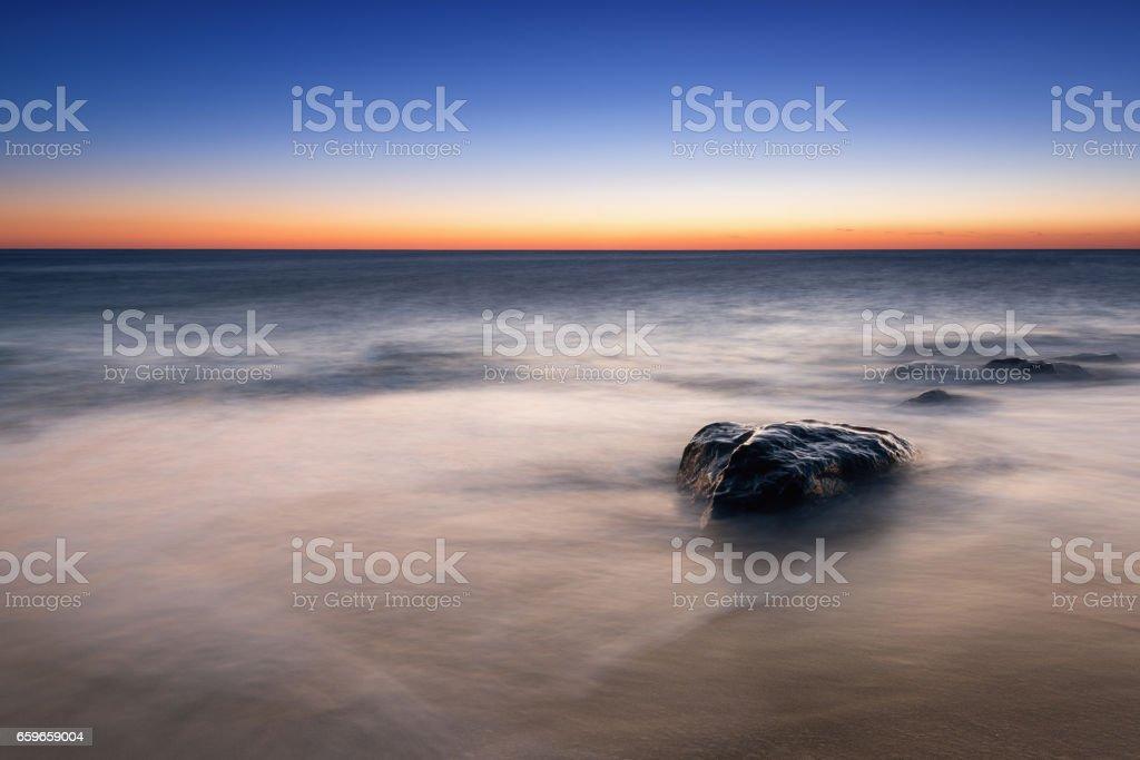 Misty rock seascape sunrise stock photo