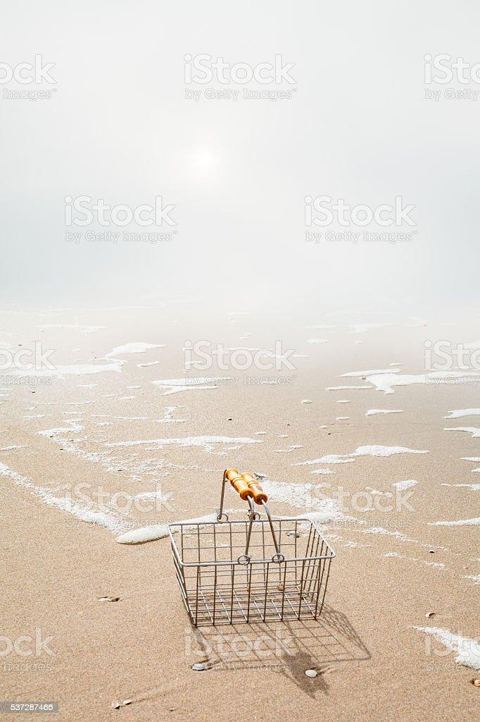 Misty sun on sandy beach with small shopping basket stock photo