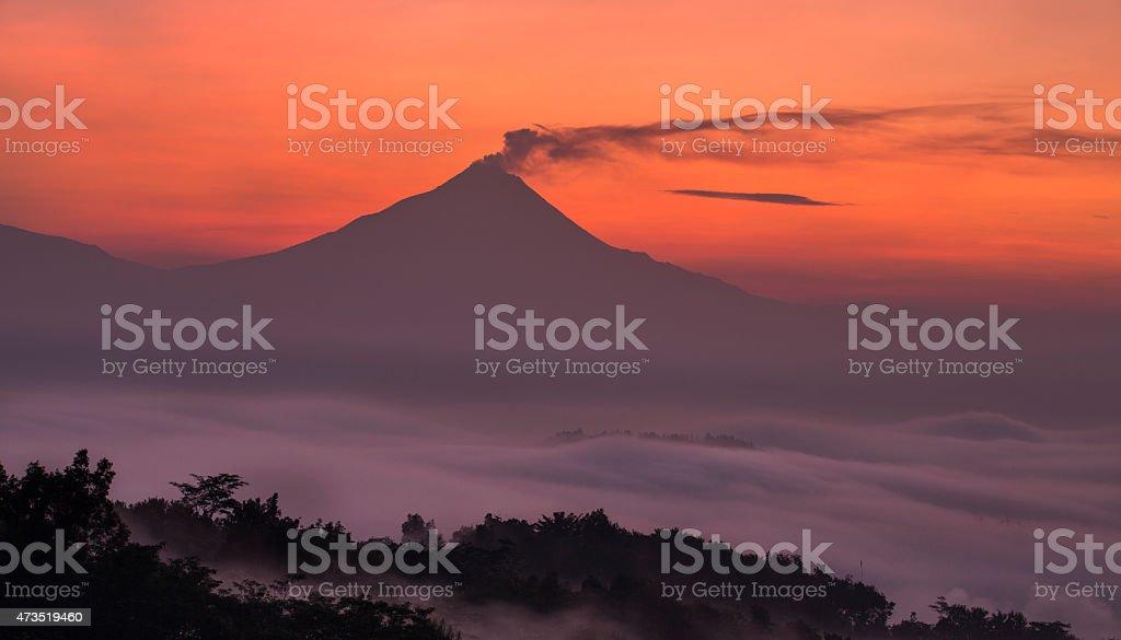 Misty sunrise over volcano mountain Merapi in Java in Indonesia stock photo