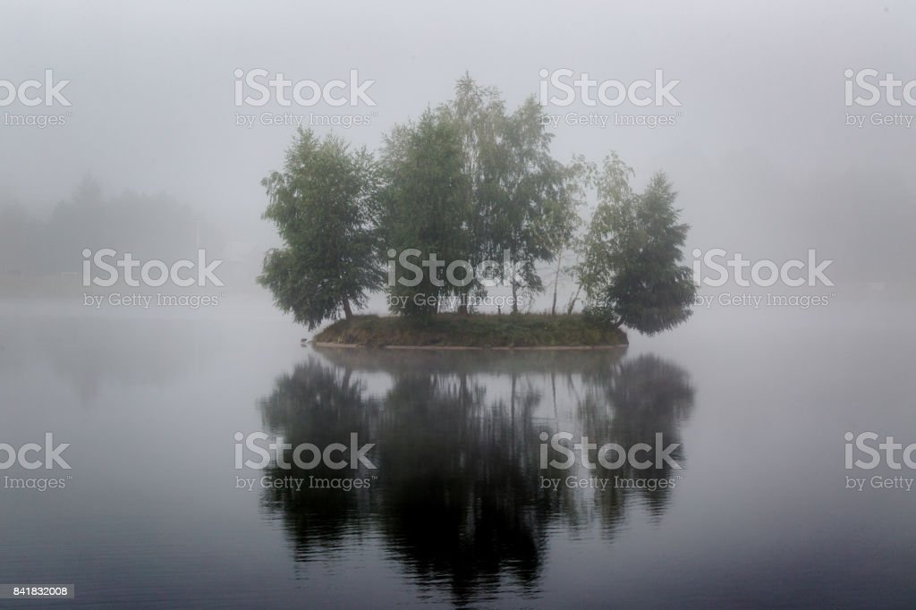 Misty very small island on foggy lake in morning hours light stock photo