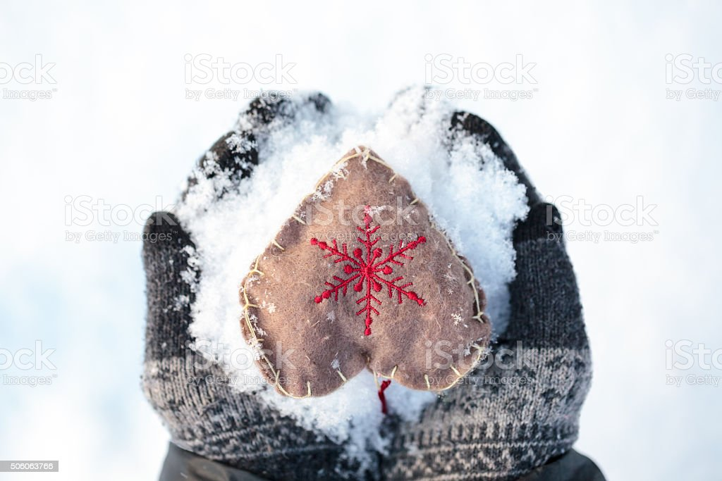 Mittens with heart on snow winter holidays concept stock photo