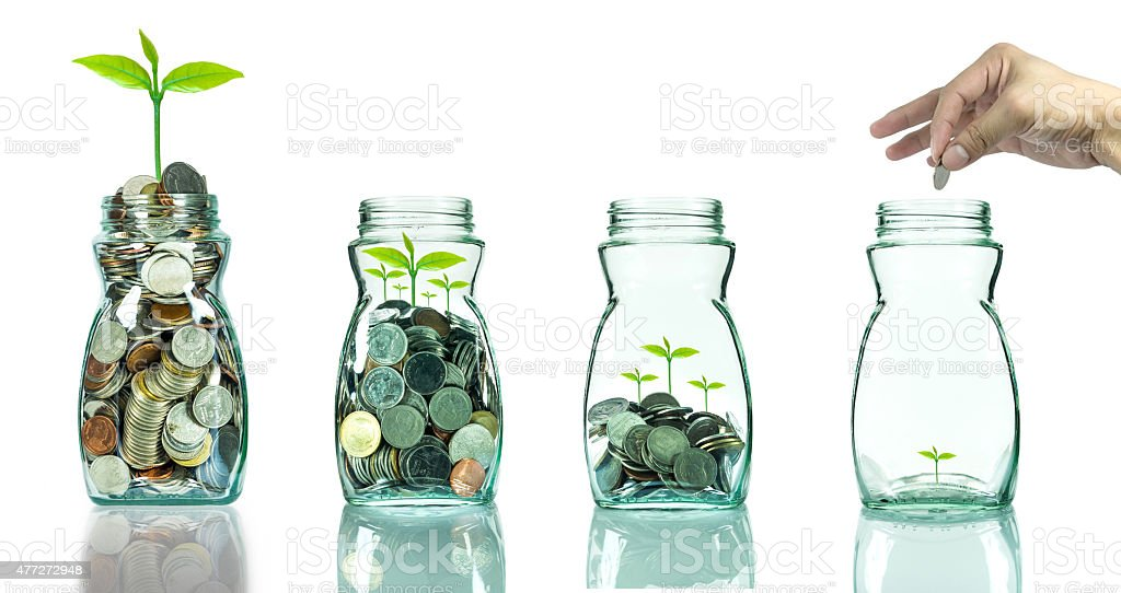 Mix coins and seed in clear blottle on white background stock photo