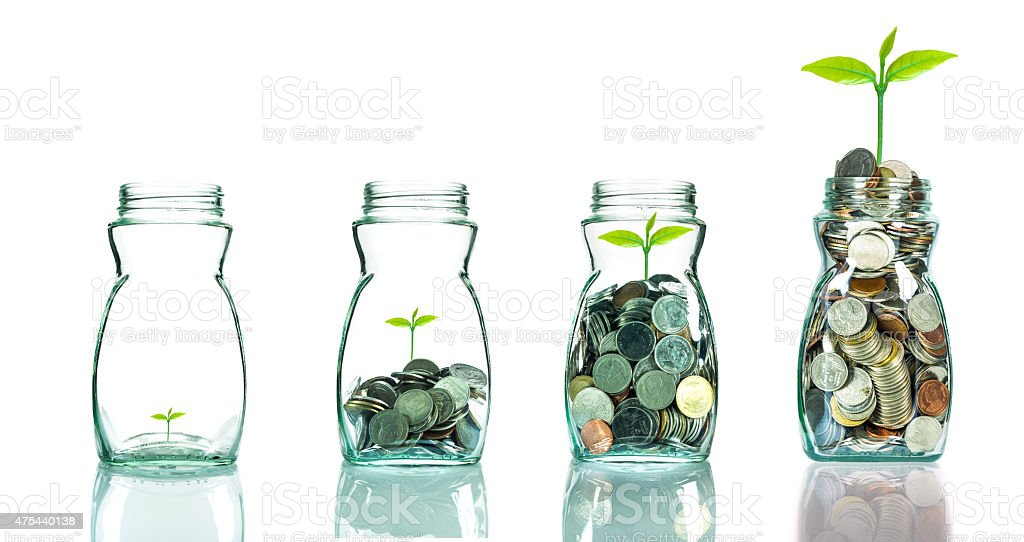 Mix coins and seed in clear bottle on white background stock photo