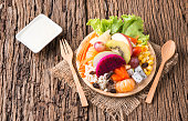 Mix fruits salad on wood plate and wood background