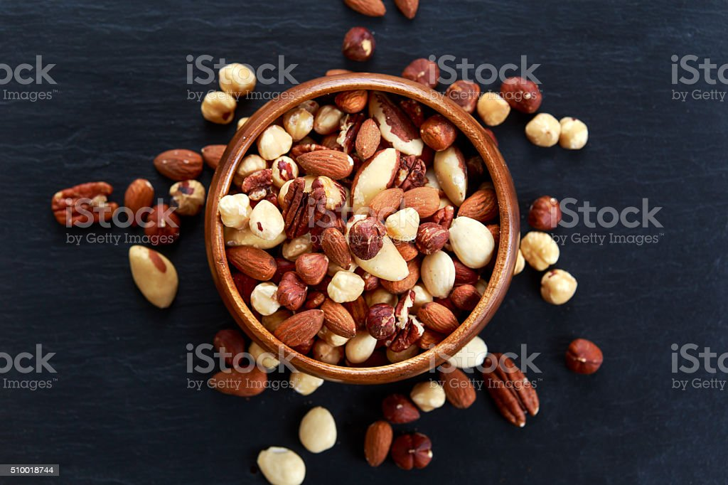 mix nuts in wooden bowls on old blue stone background stock photo