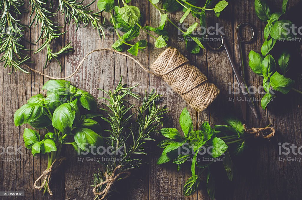 Mix of fresh herbs from garden on wooden table stock photo
