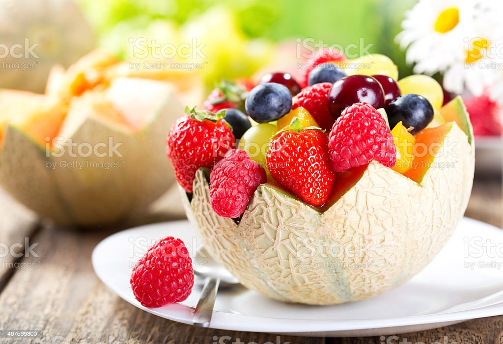 Mix of fruits making a salad on white plate stock photo