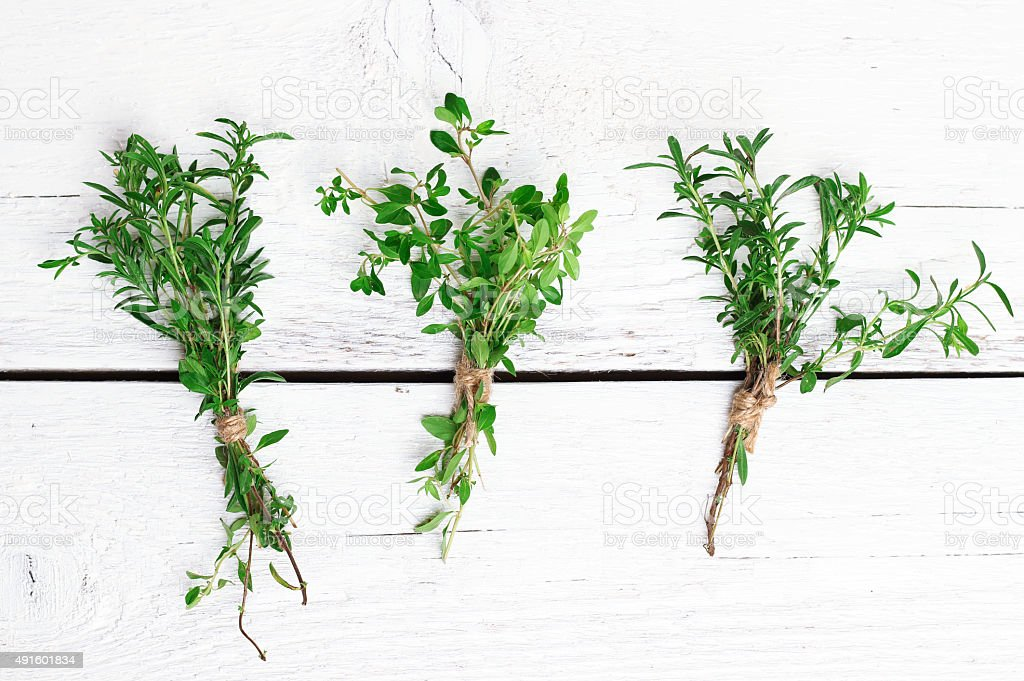 Mix of herbs on a wooden table, savory, thyme stock photo