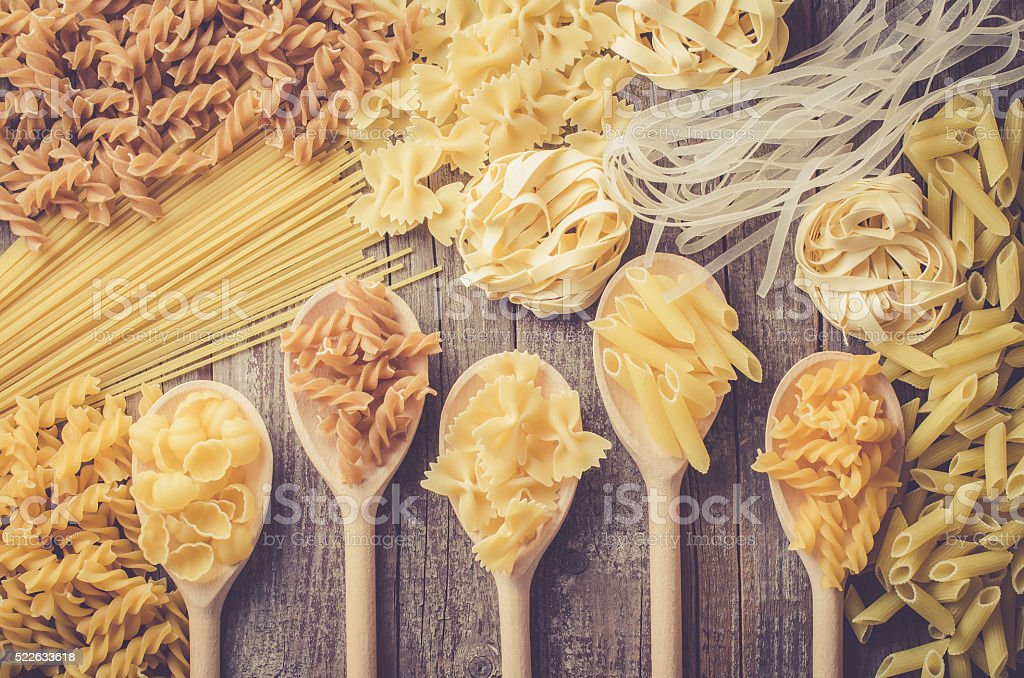 Mix of pasta on wooden table stock photo