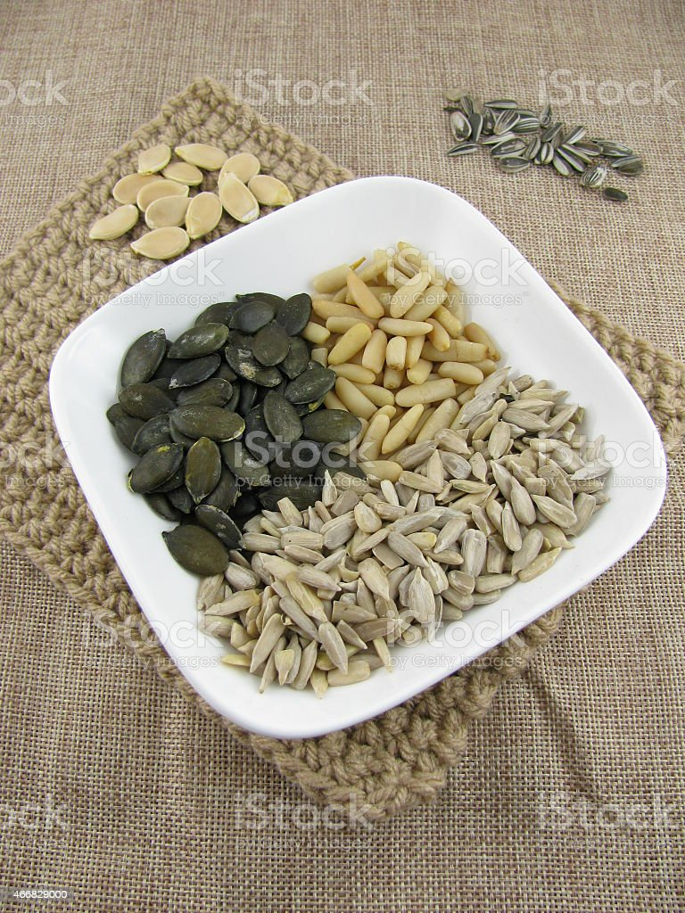 Mix of pumpkin seeds, sunflower seeds and pine nuts stock photo