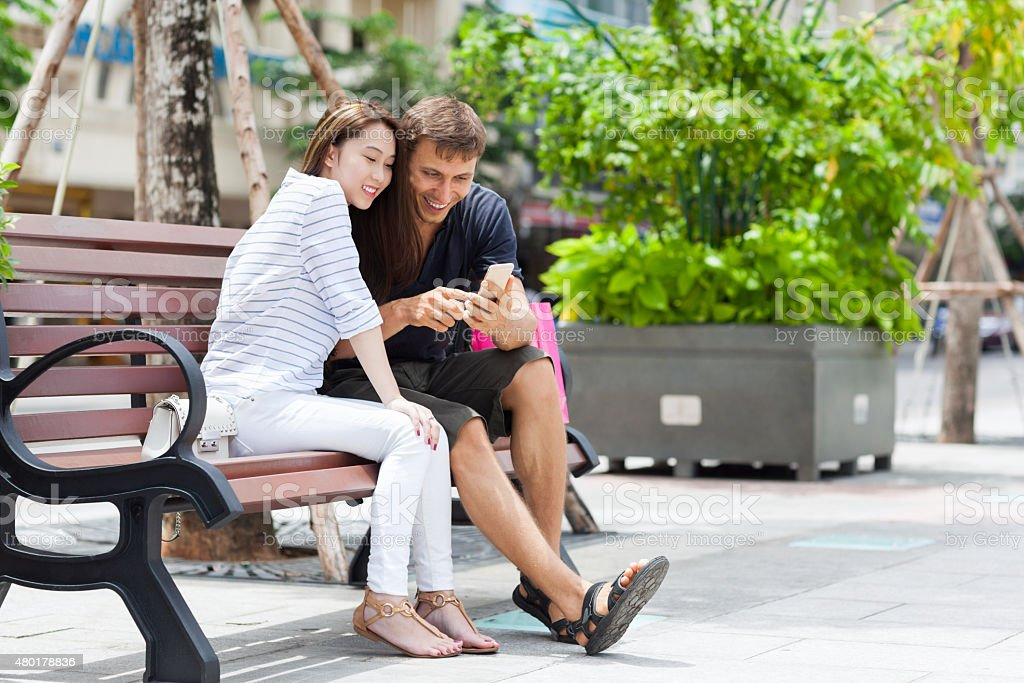 Mix Race Couple Using Cell Smart Phone Sitting  Smile stock photo