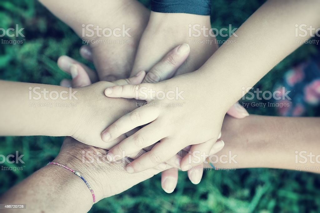Mixed Ages Team Joining Hands stock photo