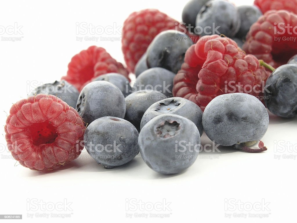Mixed blueberries and raspberries on a white background royalty-free stock photo