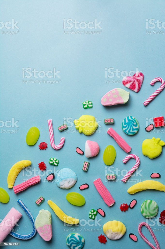 mixed collection of colorful candy, on blue background stock photo