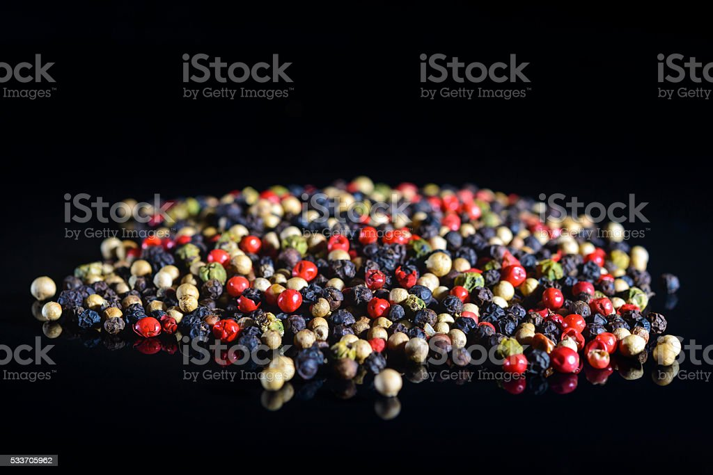 Mixed colored peppercorns on a black background stock photo