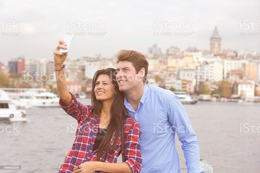 Mixed couple taking a selfie with Galata tower stock photo