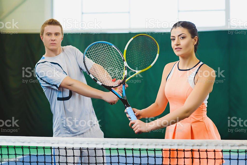 Mixed Doubles player hitting tennis ball, partner standing near net stock photo