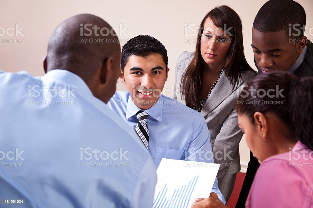 Mixed Ethnic Group of Young Adults Discussing Business Projections royalty-free stock photo