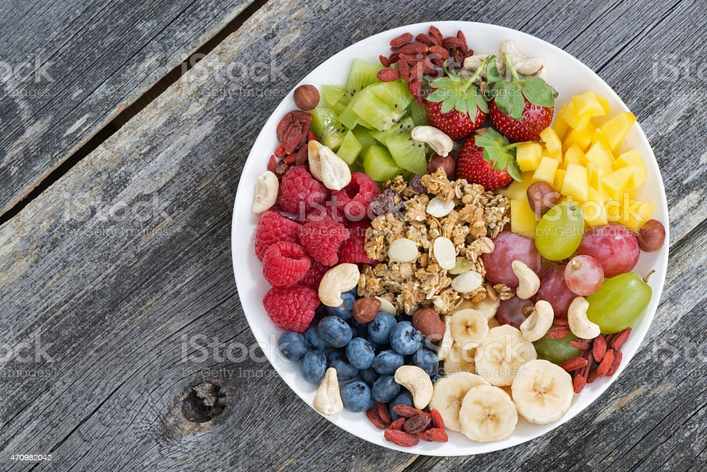Mixed fruit, nuts and granola in a white bowl on wood table stock photo