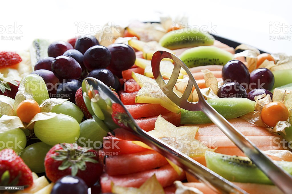 Mixed fruit platter with tongs in sunlight stock photo