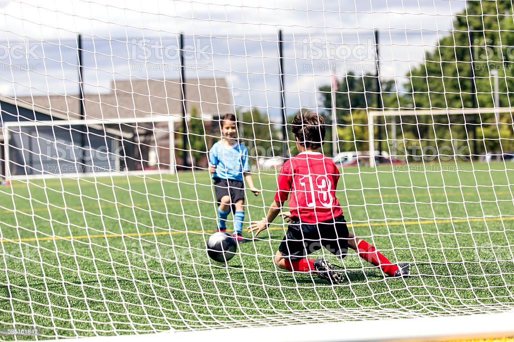 Mixed gender soccer team makes a goal attempt stock photo