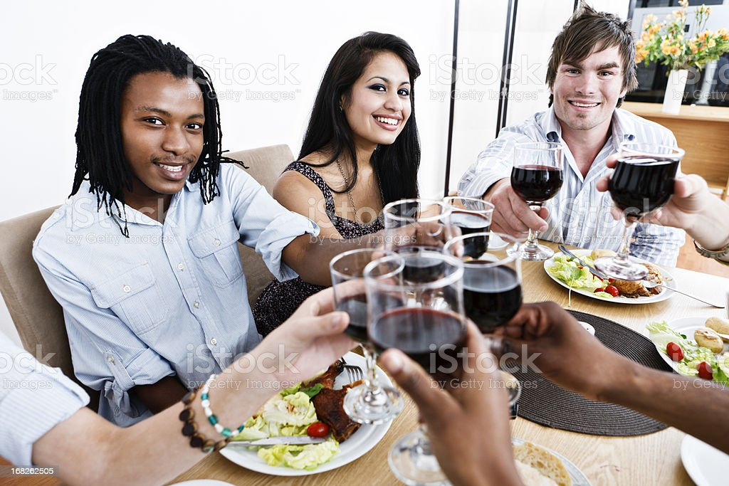 Mixed group of happy friends toasting at dinner table royalty-free stock photo